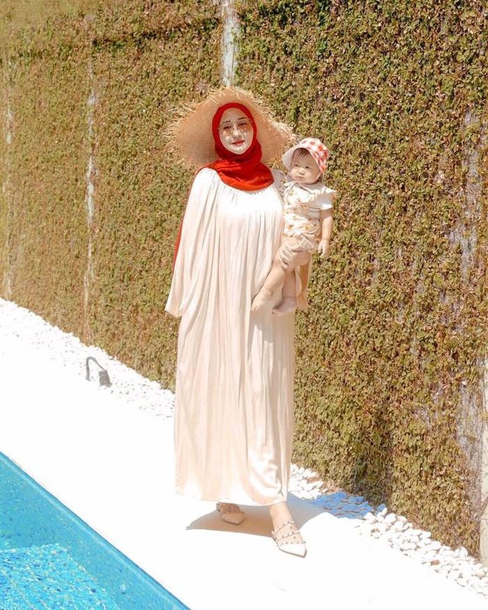 Walaupun sedang berada di rumah, Dian tampaknya sangat senang mengajak Rumi berfoto bersama. Kali ini berpose di pinggir kolam renang dengan mengenakan home dress dipadukan dengan hijab merah, lengkap dengan topi ala pantai. /Foto:@dianpelangi