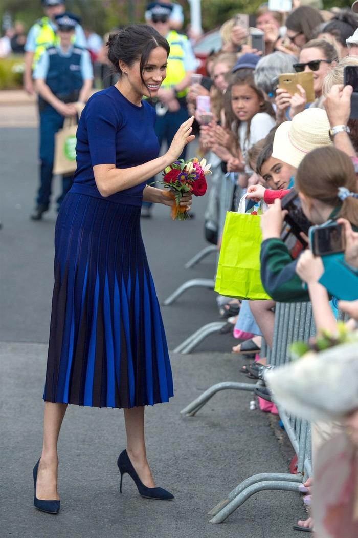 Selama mengandung, Meghan seringkali terlihat stylish di segala kesempatan. Seperti saat ia berkunjung ke Rotorua, New Zealand, pada tahun 2018 lalu Meghan terlihat manis dengan paduan pleated skirt biru tua dari Givenchy dan heels berwarna senada. (Foto: harpersbazaar.com)