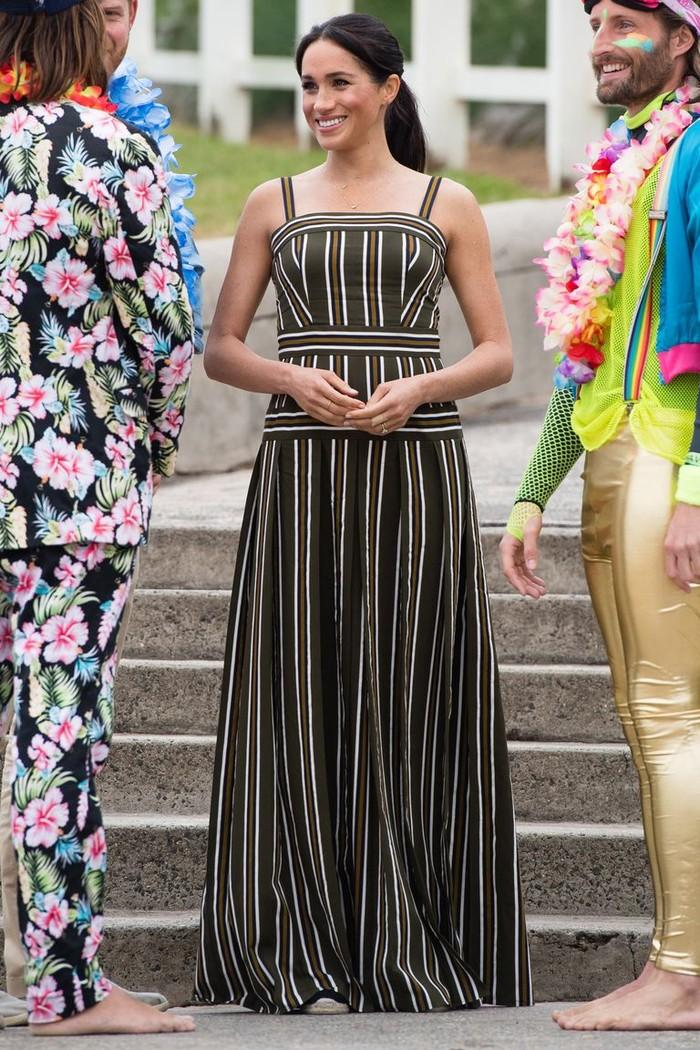 Walau sedang mengandung, ia tetap tidak meninggalkan tugasnya. Dengan tetap memperhatikan penampilan, Meghan memilih untuk mengenakan striped maxi dress longgar dari Martin Grant yang membuatnya tetap nyaman. (Foto: harpersbazaar.com