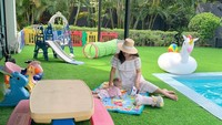 <p>Halaman tersebut disulap menjadi taman bermain yang dilengkapi dengan furnitur, perosotan, dan berbagai mainan untuk si kecil. Whulandary Herman juga sering mengajak anak bungsunya bersantai di atas karpet yang digelar di halaman. (Foto: Instagram @whulandary)</p>