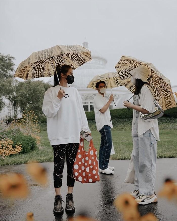 Masih mengenakan brand lokal Erigo, mereka juga menyempatkan berkunjung ke New York Botanical Garden. Enzy Storia, Febby Rastanty, dan Omar Daniel kompak mengenakan baju putih dan payung bermotif ciri khas Yayoi Kusama. Foto: instagram.com/enzystoria