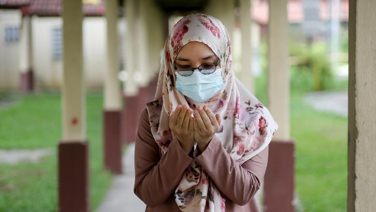 A female adult is putting both hands together for 'doa' (Muslim way of praying) during partial lockdown in Malaysia.