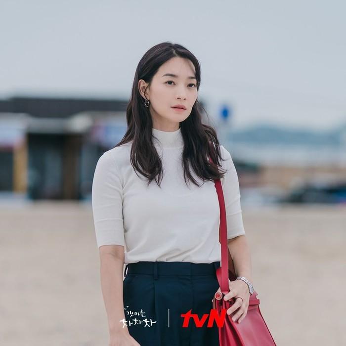 Potret Shin Min Ah tampil dengan fashion simpel turtle neck putih dengan bawahan berwarna biru dipakai ketika ia mengunjungi desa Gongjin untuk pertama kalinya, kala mengingat momen bersama dengan mendiang kedua orang tuanya./Foto: instagram.com/netflixid