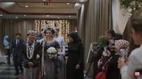 <p>Prosesi pernikahan dilanjutkan dengan acara resepsi. Mereka berganti pakaian dengan memakai baju adat bernuansa lebih gelap. Para tamu menyoroti mereka ketika memasuki ruangan. (Foto: YouTube Tess & Tom)</p>