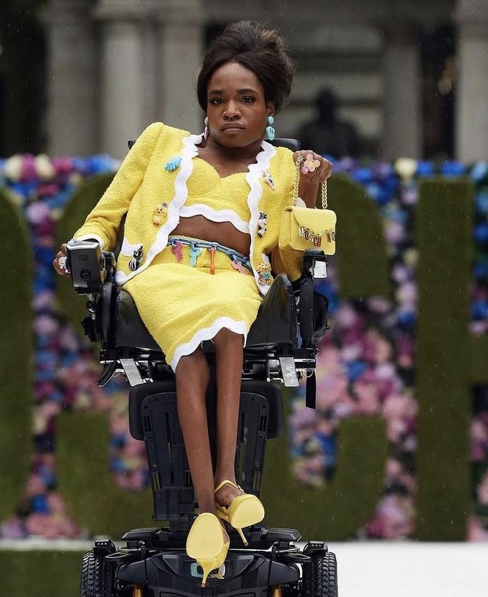 Spirit inklusif juga menjadi bagian dari fashion show Moschino ini di mana menunjuk seorang model transgender dan penyandang disabilitas untuk tampil. Aaron Rose Philip debut sebagai model Moschino musim ini dengan mengenakan setelan dan tas mini. Keren bukan? Foto: instagram.com/ellethailandofficial