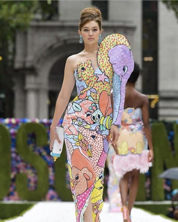 Hadirkan eksplorasi warna pada koleksinya, Moschino menggandeng Gigi Hadid sebagai model dengan membawa botol bayi. Aksinya menggigit botol bayi di tengah runway jadi hal menarik lainnya dari show rumah mode Italia ini. Foto: instagram.com/moschino
