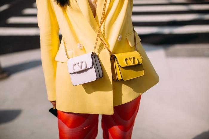 Jika ingin mengikuti tren tas mini namun terlampau membawa banyak bawaan, mengapa tidak untuk membawa dua tas sekaligus yang berukuran sama. Kenakan menyilang agar terlihat lebih stylish dan nggak berlebihan. Foto: livingly.com/IMAXtree