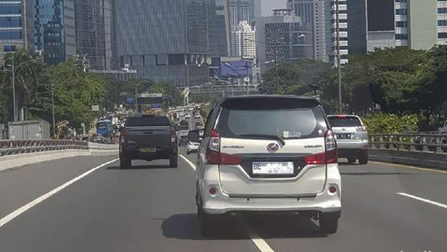 Mobil low MPV dengan pelat nomor kendaraan dasar putih tulisan hitam kedapatan tengah melaju di jalan tol dalam kota mengarah ke Merak.