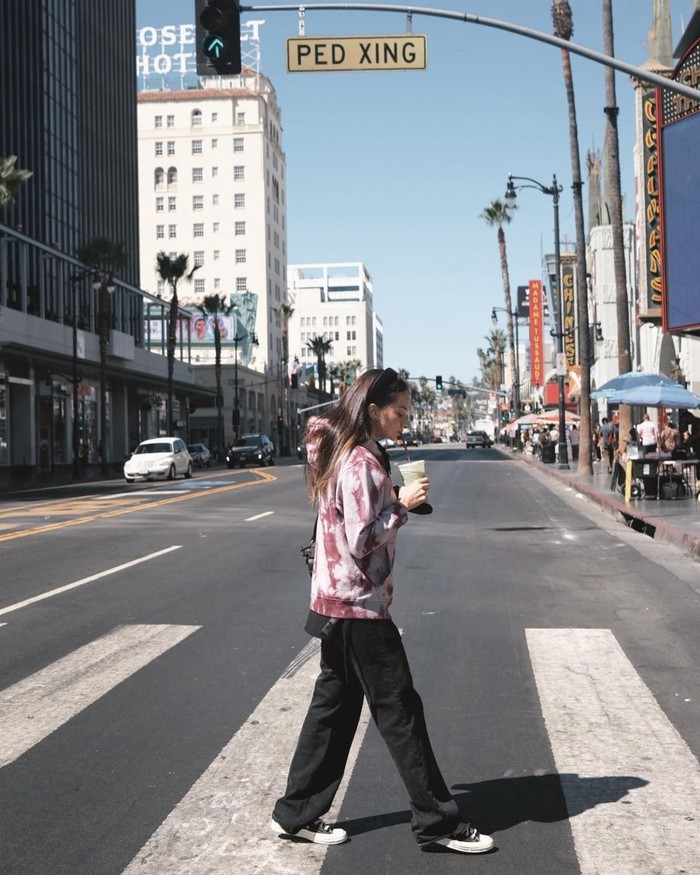 OOTD Enzy memang kebanyakan bergaya hypebeast, seperti saat menyusuri Hollywood Walk of Fame. Perpaduan hoodie dengan motif tie dye dan straight jeans hitam yang membuat dirinya tampak santai dengan gaya berbeda. /Foto: instagram.com/@enzystoria