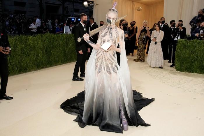 Grimes membawa nuansa teatrikal ke red carpet Met Gala 2021. Ia memakai gaun Iris Van Herpen sembari membawa 'pedang' sebagai aksesori.Foto: Getty Images
