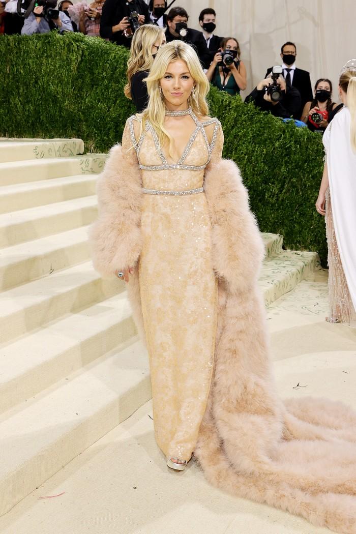 Sienna Miller memilih gaun bernuansa blush dalam material lace yang romantis. Foto: Getty Images