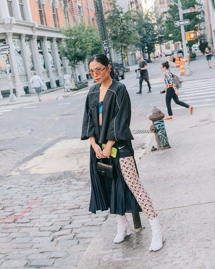 Bukan Ayla Dimitri kalau tidak fashionable. Dengan outfit serba hitam, ia tampil berani dengan rok aksen slit, dipadukan dengan stoking dan boots berwarna putih. (@ayladimitri)