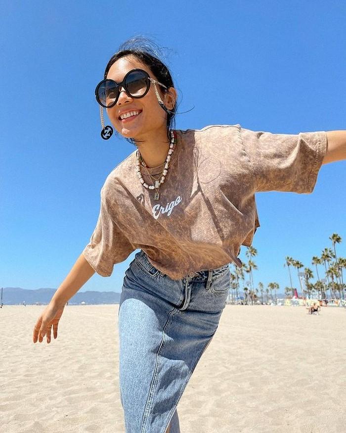 Tampilan yang lebih santai dipakainya saat mengunjungi sebuah pantai di Santa Monica. Ia mengenakan rok denim dan kaus bermotif tie die. Kacamata andalan membuatnya terlihat catchy. Bisa jadi inspirasi outfit liburan nih. (@ayladimitri)