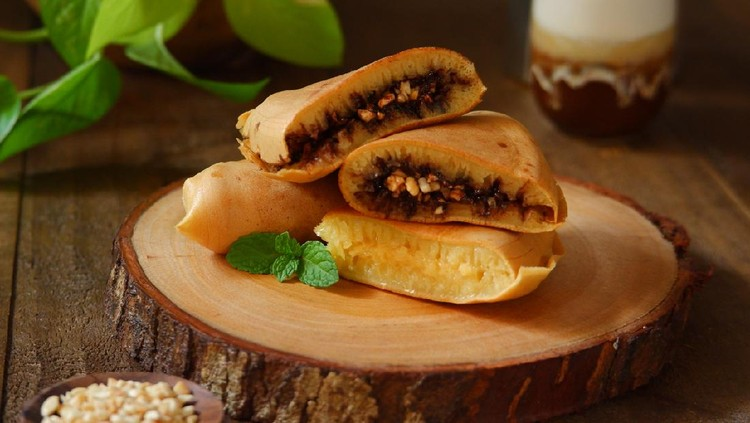 Martabak manis or traditional sweet pancake with various topping on a wooden cutting board