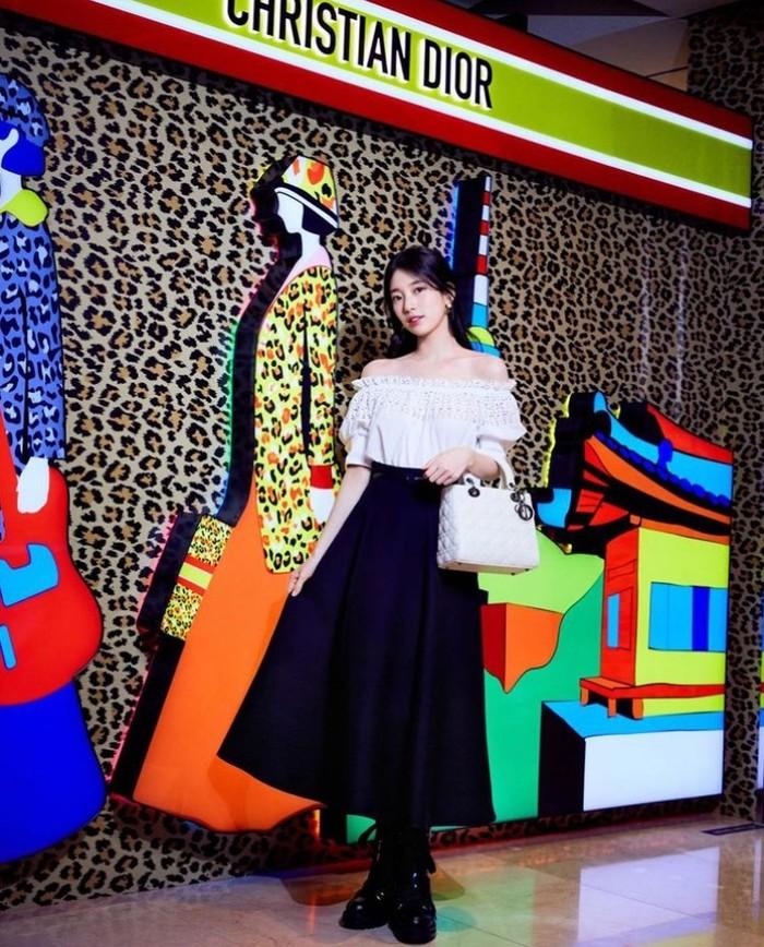Selain dengan rok pensil, Beauties juga dapat memadupadankan atasan off-shoulder dengan Mid-Length Skirt seperti yang dikenakan Suzy saat menghadiri Pop-Up Store Dior, nih./ Foto: Instagram.com/skuukzky