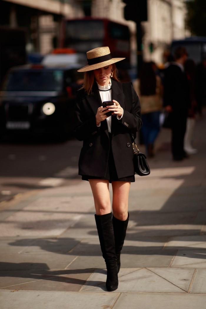 Padanan blazer dengan rok mini dan boots menampilkan nuansa retro ala era '60an. Serta terasa lebih chic dan modern berkat koordinasi warna serba hitam. Foto: livingly.com/IMAXtree