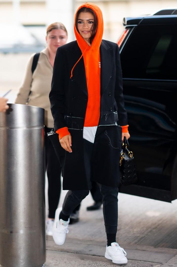 Untuk kamu yang suka dengan gaya sporty casual, sepertinya gaya Zendaya satu ini bisa kalian tiru.Ia tampak nyaman dengan sweater orange menyala yang dibalut dengan long coat berwarna hitam, kombinasi yang unik bukan? /Foto: Getty images/Gotham