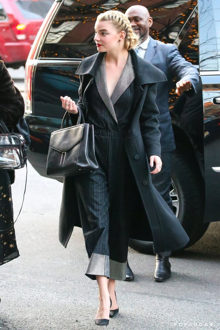 Anya Taylor-Joy terlihat stylish mengenakan busana model jumpsuit motif stripes yang dipadukan dengan luaran berupa long coat warna hitam yang membuat gayanya makin memukau. /Foto: Getty Images