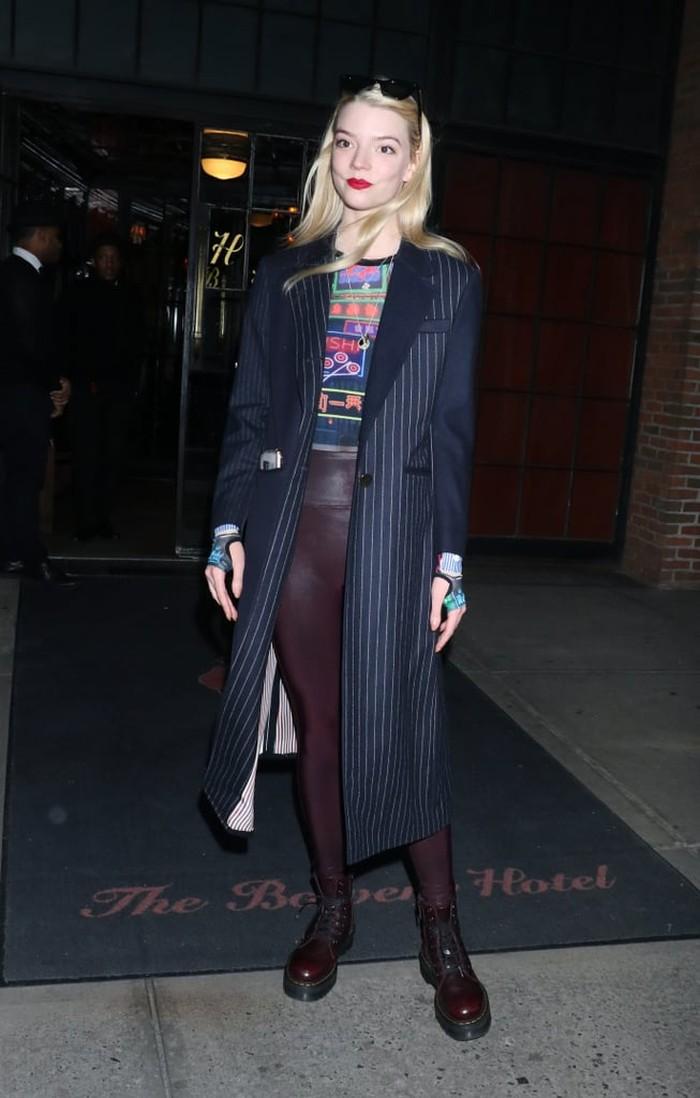Anya terlihat bergaya edgy untuk tampilan street style-nya kali ini, dengan legging warna maroon yang dipadukan bersama sepatu docmart. Tak hanya itu, Anya juga memadukan atasan motif tersebut dengan coat motif stripes./Foto: Getty Images