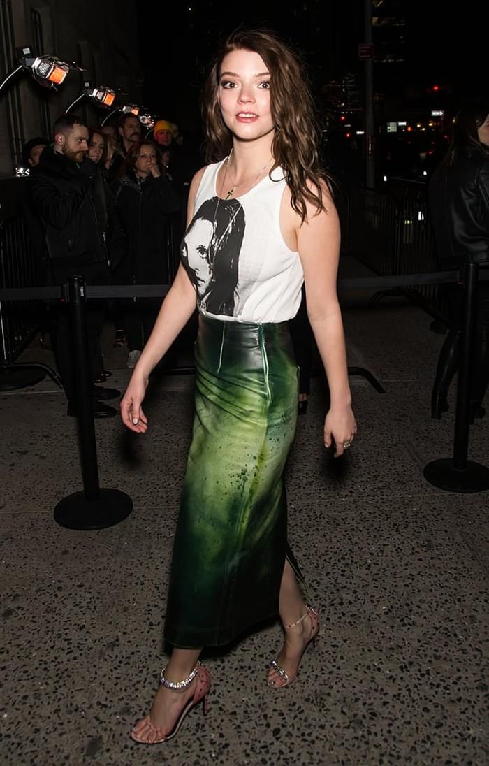 Anya terlihat percaya diri memadukan tank top warna putih dengan rok kulit bernuansa warna hijau. Ia juga turut bergaya modis mengenakan heels berhiaskan kristal yang menyempurnakan tampilan street style-nya./Foto: Getty Images