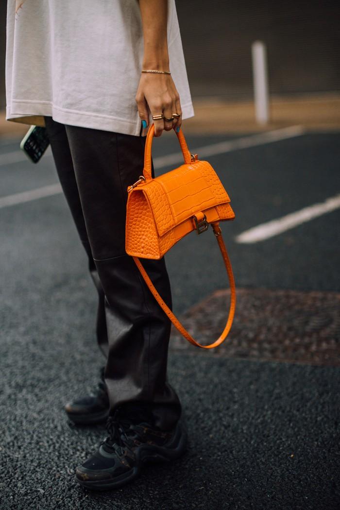 Pilihan tas dalam warna orange memberi nuansa quirky pada tampilan monokrom. Foto: livingly.com/IMAXtree