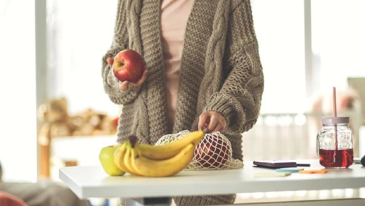 Ilustrasi wanita makan buah apel dan pisang