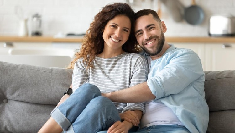 Portrait of young 35s just married couple in love posing photo shooting seated on couch in modern studio apartments, concept of capture happy moment, harmonic relationships, care and sincere feelings
