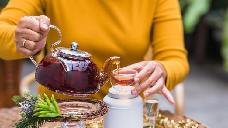 Woman pouring tea from glass pot into cup, Tea ceremony concept