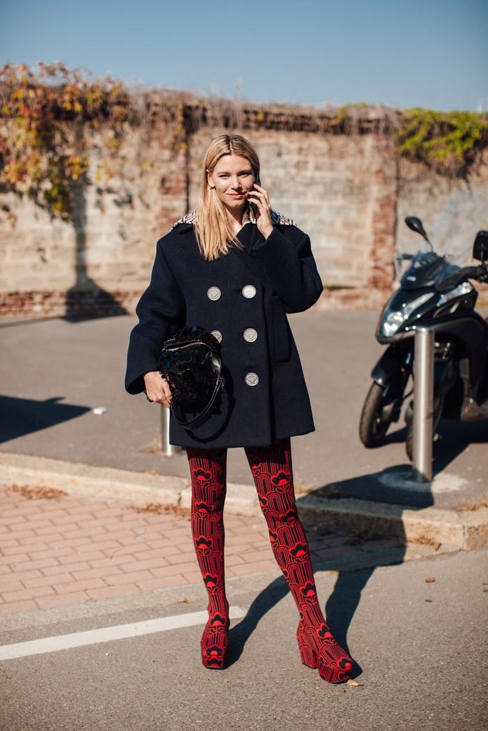 Kejutan hadir dari oversized coat yang klasik ketika dikenakan bersama socks boots motif grafis dalam warna merah. Foto: livingly.com/IMAXtree