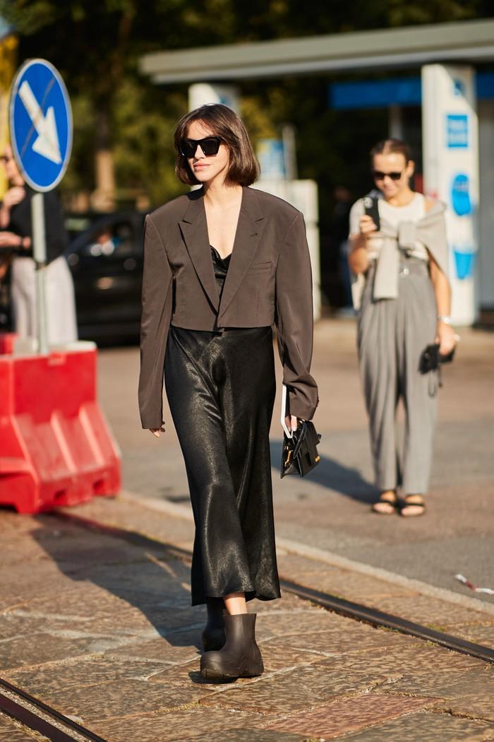Slip dress tak harus selalu dikenakan bersama heels, coba padukan bersama rain boots dan cropped jacket untuk gaya yang lebih modern. Foto: livingly.com/IMAXtree