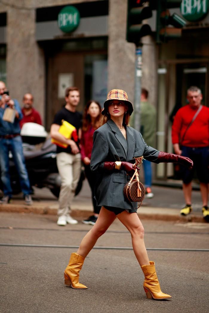 Blazer yang formal dapat tampil edgy berkat potongan serupa cape dan ketika dikenakan bersama ankle boots dan bucket hat. Foto: livingly.com/IMAXtree