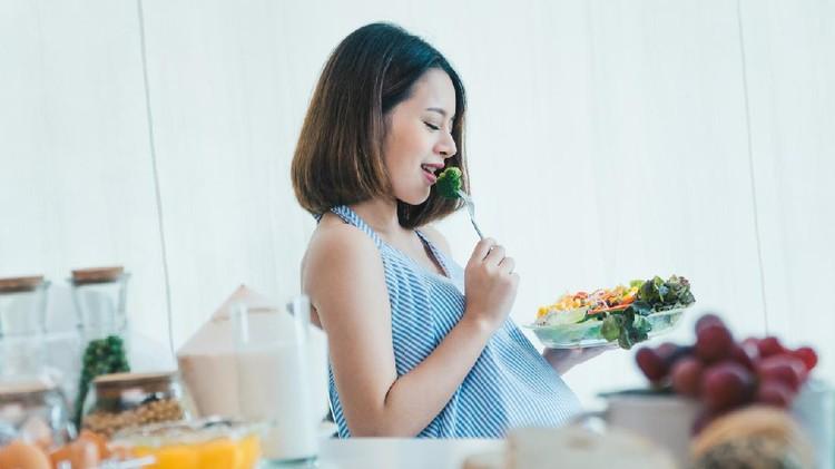 Ilustrasi ibu hamil makan sayuran