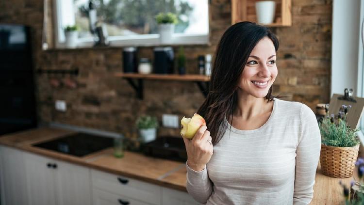 Ilustrasi wanita makan buah apel