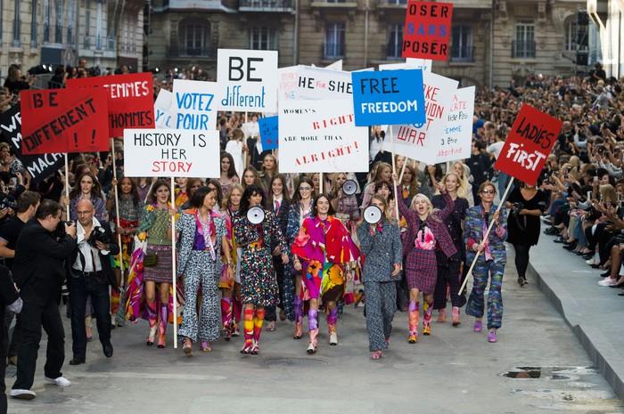 Secara mengejutkan dalam panggung berupa jalanan kota Paris untuk koleksi spring/summer 2015 ditutup dengan para model yang berakting melakukan demonstrasi. Foto: livingly.com/IMAXtree