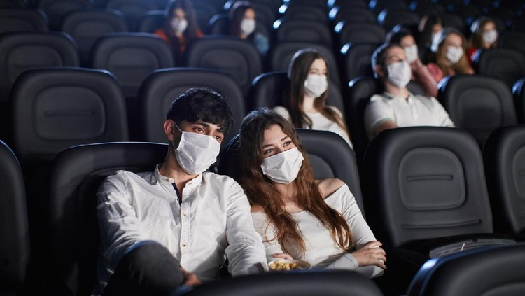 Selective focus of man and woman enjoying film during world pandemic, looking at screen. Young caucasian audience watching movie in cinema, wearing white face masks. Social distancing concept.