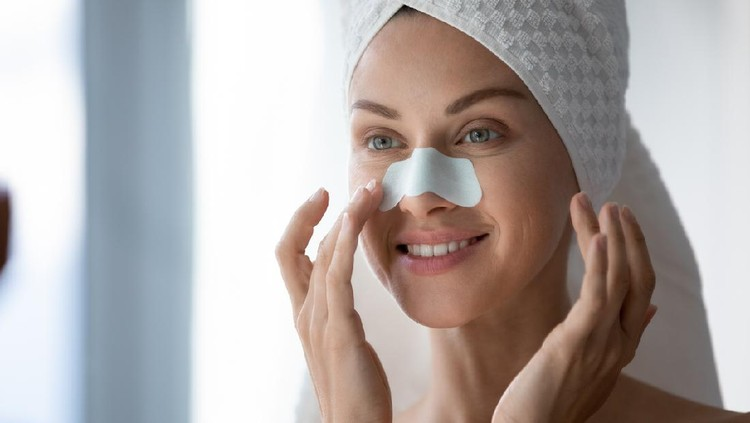 Close up 30s woman after shower with towel on head use white cleansing nose strips deep purifying treatment to unclog pores prevent remove blackheads, leaving skin clear and smooth, skincare concept