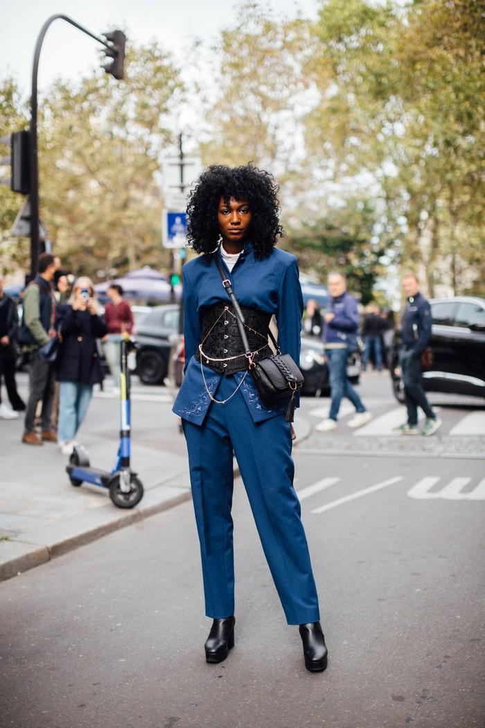 Aksi tak biasa lewat aksen korset pada setelan jas. Keep it cool dengan padanan aksesori serba hitam. Foto: livingly.com/IMAXtree