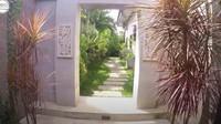 <p>Rumah Eks TKW Banyuwangi ini tampak asri. Ada pintu dan jalan setapak yang menghubungkan halaman depan rumah menuju ke halaman belakang rumah. (Foto: Youtube BAJIDOT VLOG)</p>