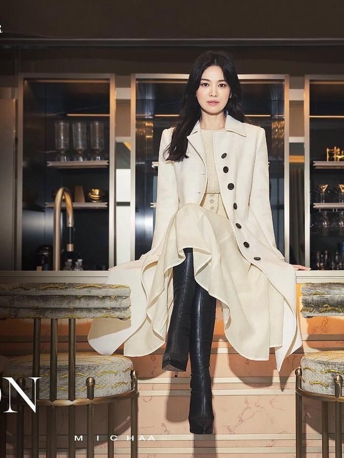 Melalui konsep Be An Icon, Song Hye Kyo banyak menunjukkan sisi minimalis dan elegan untuk koleksi yang diluncurkan. Perpaduan long blazer dengan warna khaki serta sepasang leather boots berwarna hitam membuat penampilannya makin berkelas./Foto: instagram.com/michaachannel