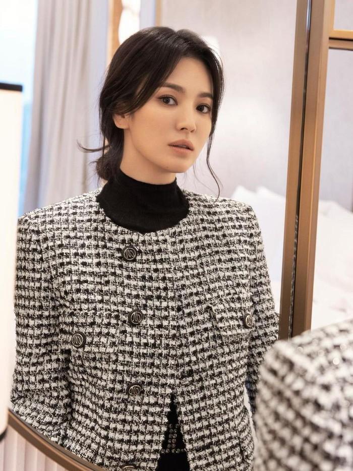 Untuk gaya selanjutnya, Song Hye Kyo tampil dengan gaya preppy look mengenakan inner berwarna hitam yang dipadukan dengan jaket model tweed. Warna hitam, putih, serta abu-abu membuat gaya minimalisnya makin menonjol. Tak lupa, Song Hye Kyo mengenakan riasan minimalis untuk melengkapi penampilannya./Foto: Yeongjun Kim