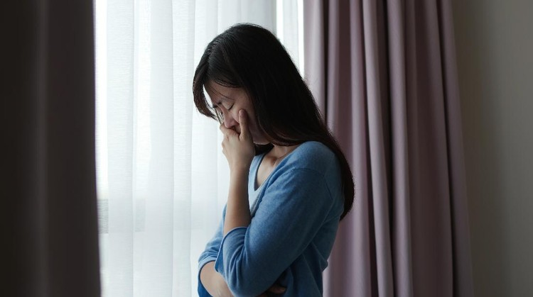 asian depression sad woman is standing by windows alone at home and thinking negative thoughts