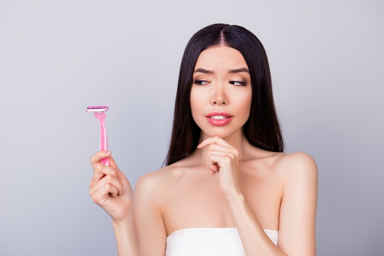 Young unsure nervous asian girl with pink shaver is standing isolated on a grey background, wrapped in a white towel, doubting if she should use it