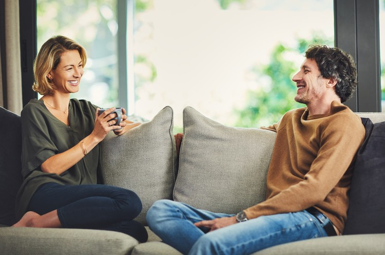 Shot of a mature couple chatting and having coffee while relaxing on the sofa at home